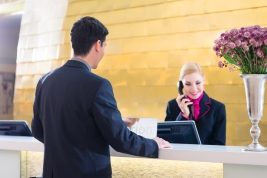 Hotel receptionist with phone and guest