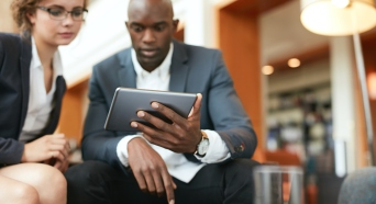 Businesspeople sitting together using digital tablet